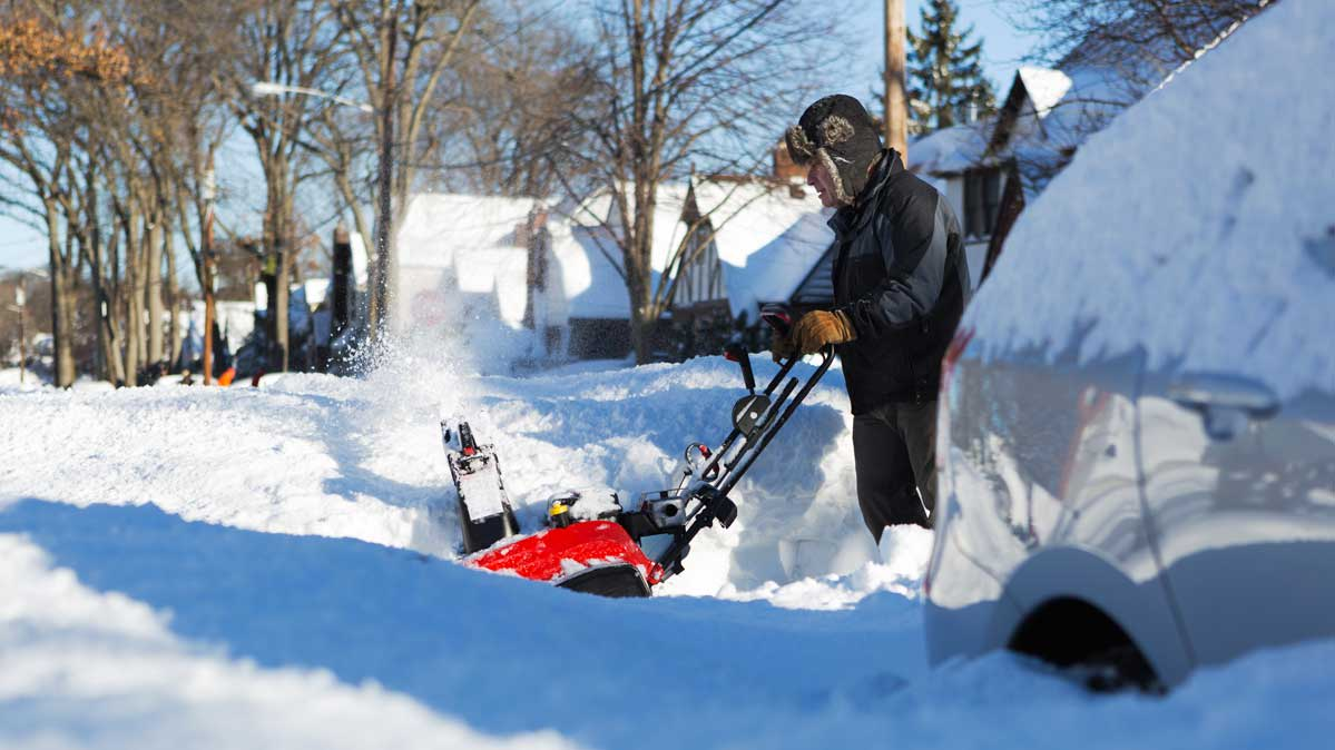 A person operating a snow blower in deep snow