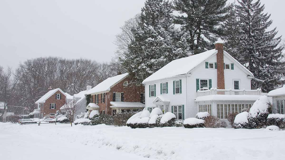 A series of suburban homes during a winter storm