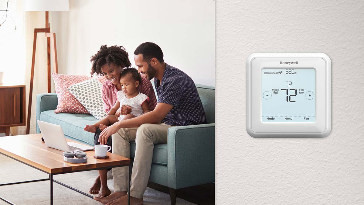 A programmable thermostat on a wall next to a family sitting in their living room.
