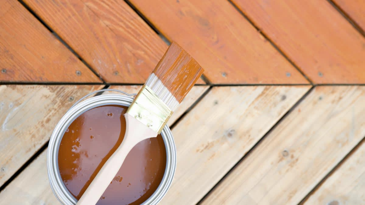 A paint brush resting on a bucket of deck stain.