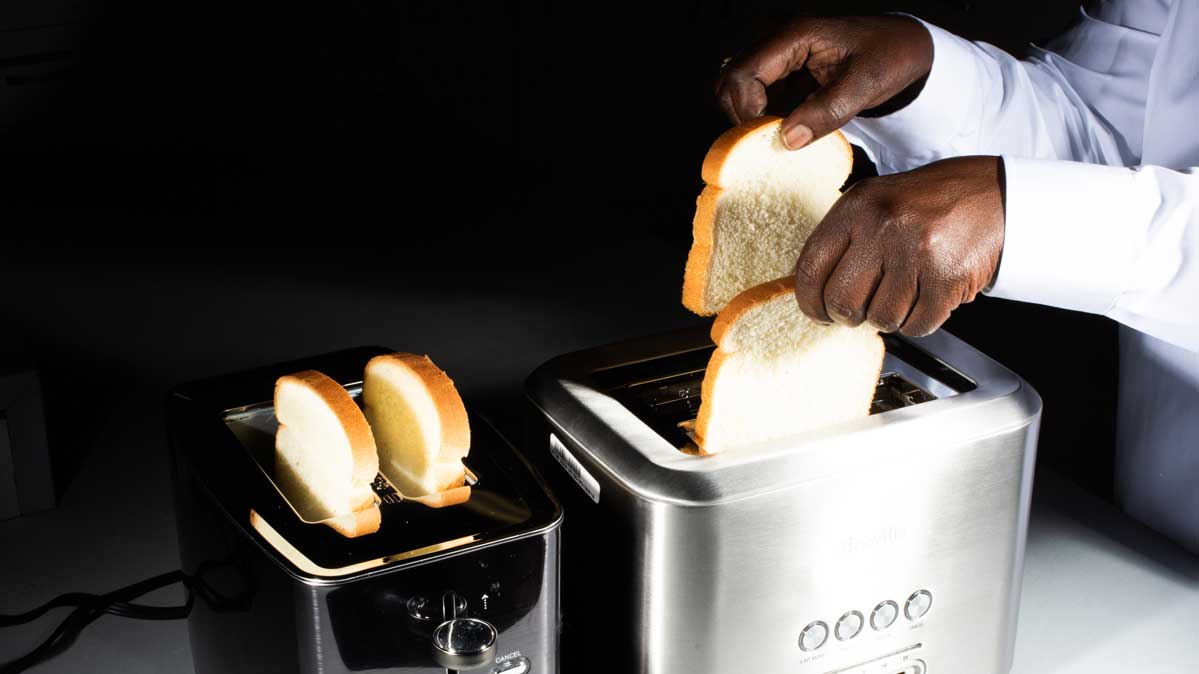 Two slices of toast pop out of two of the best toasters.