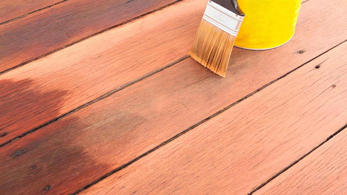 Staining a deck with a brush.