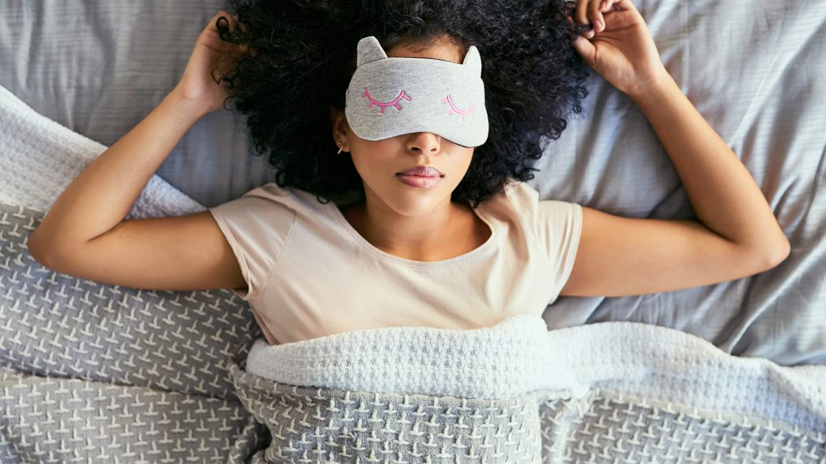 A woman sleeping on her back while wearing a sleeping mask