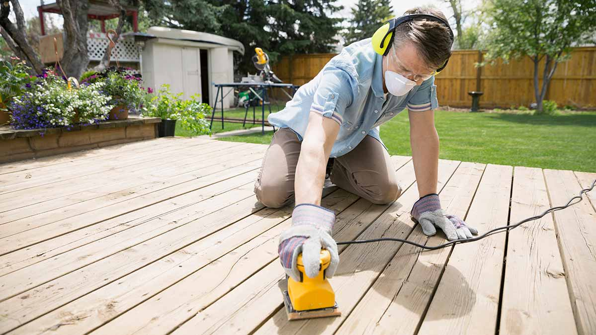 A man sanding wood deck to prep for semi-transparent wood stain