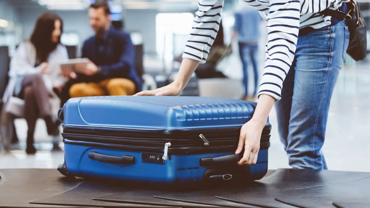 Person in blue jeans picking up checked luggage—blue, hard-sided suitcase—from baggage carousel