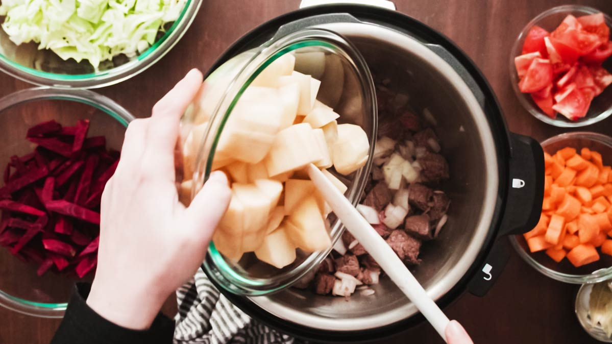 Filling a multi-cooker with nutritious ingredients.