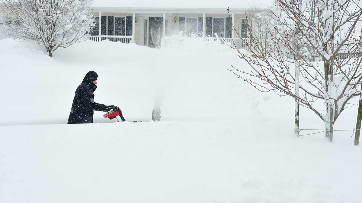 A person using a snow blower in very heavy snow