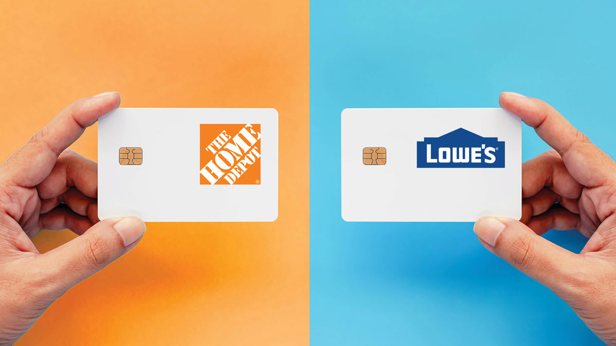 Hands holding the Home Depot Consumer Credit Card and the Lowe's Advantage Card