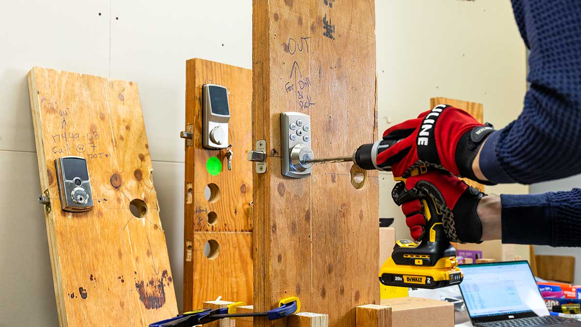 A Consumer Reports test engineer uses a cordless drill to drill through door locks.