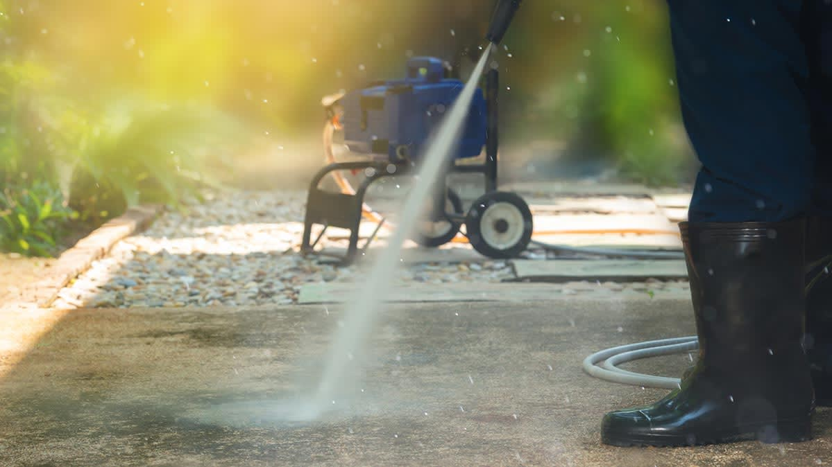 A person using a pressure washer to clean a concrete walkway.