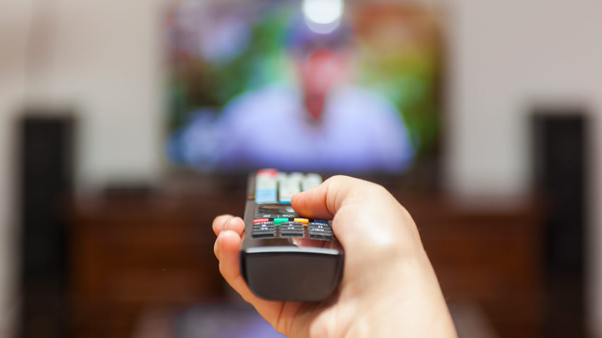 A TV viewer using a remote control to adjust settings on a TV