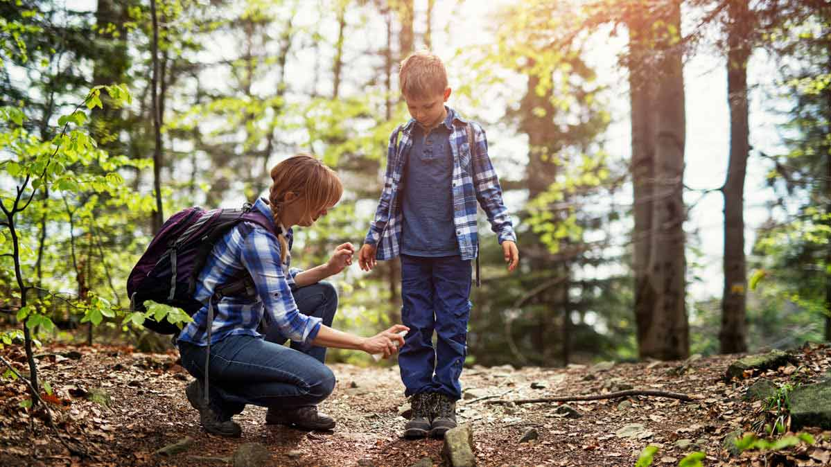 A photograph of a mother spraying insect repellent on a child's boots during a hike.