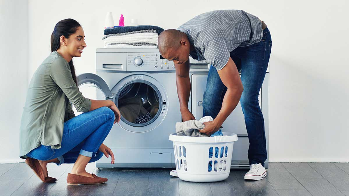 A couple going through laundry in front of a washer and dryer.
