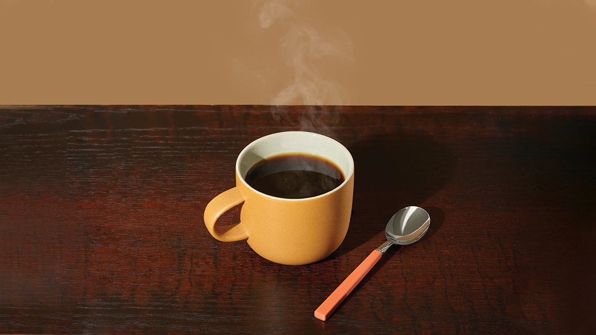 A cup of coffee with a spoon