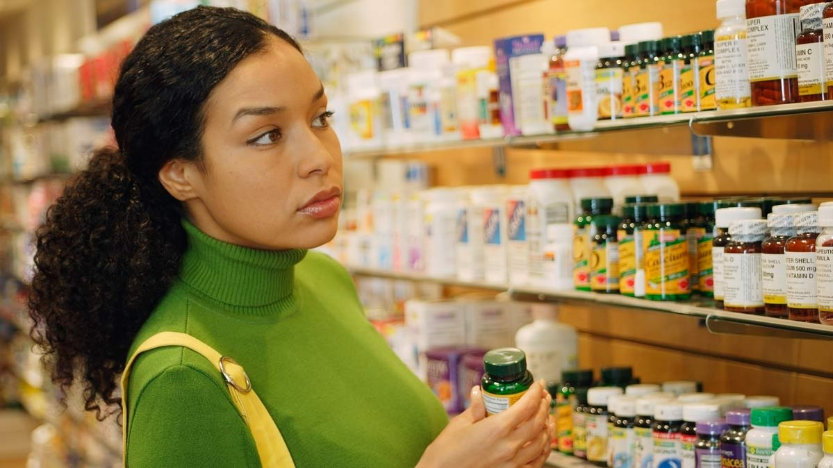 A woman choosing supplements in a store.