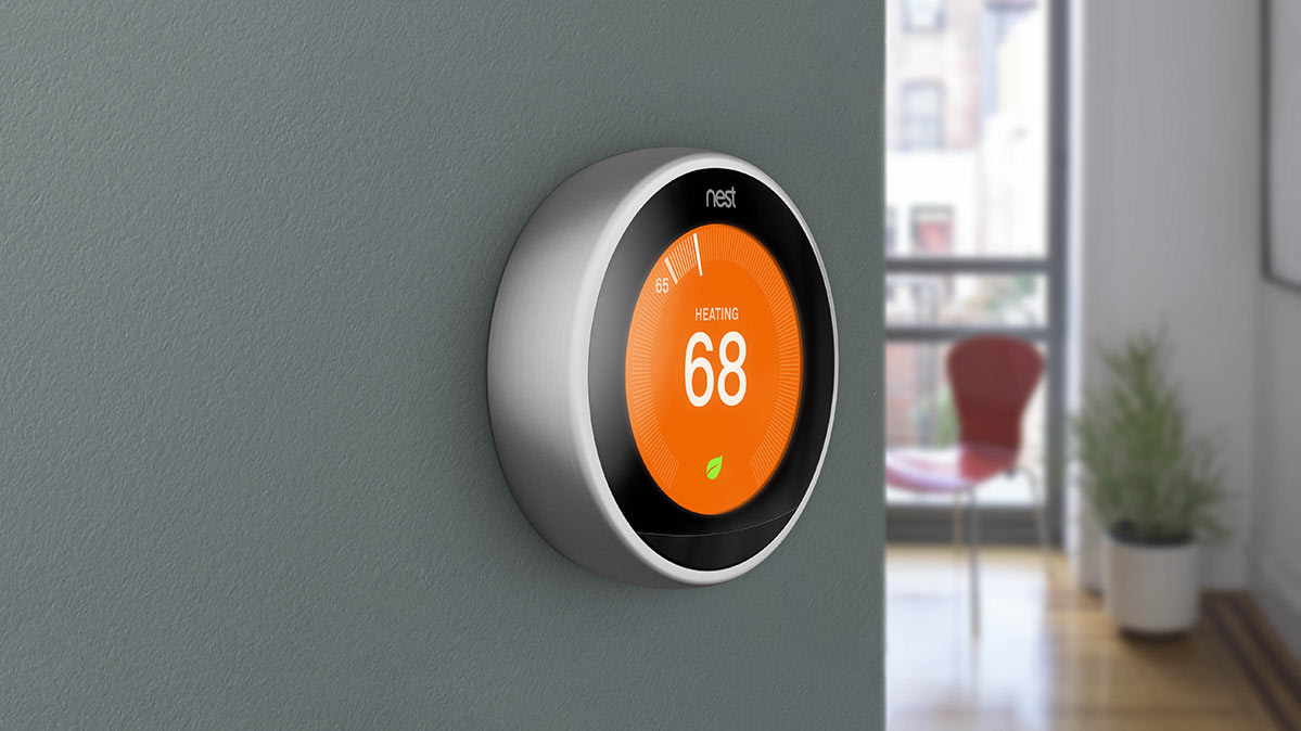 A Nest smart thermostat mounted on an interior wall in a home.