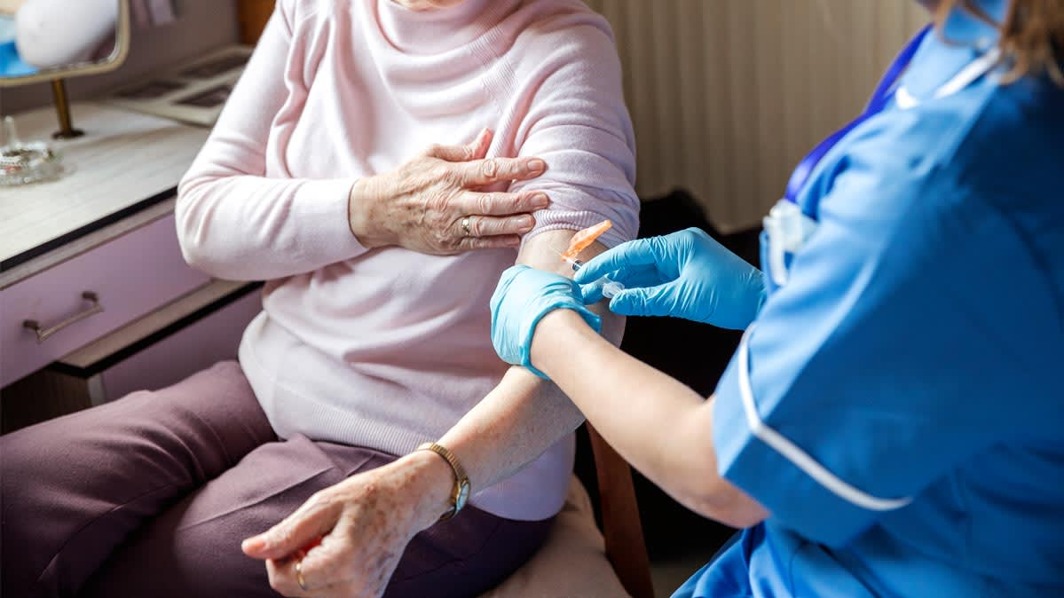 An elderly woman getting the flu shot for seniors.