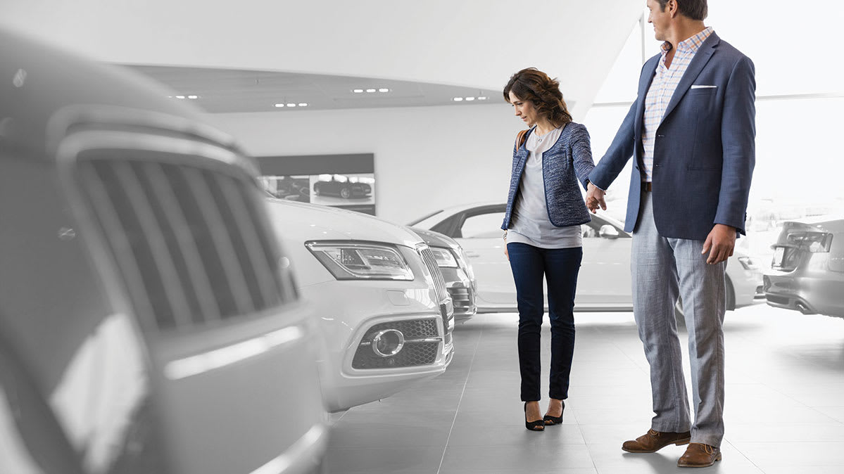 A couple looking at vehicles in a car dealership