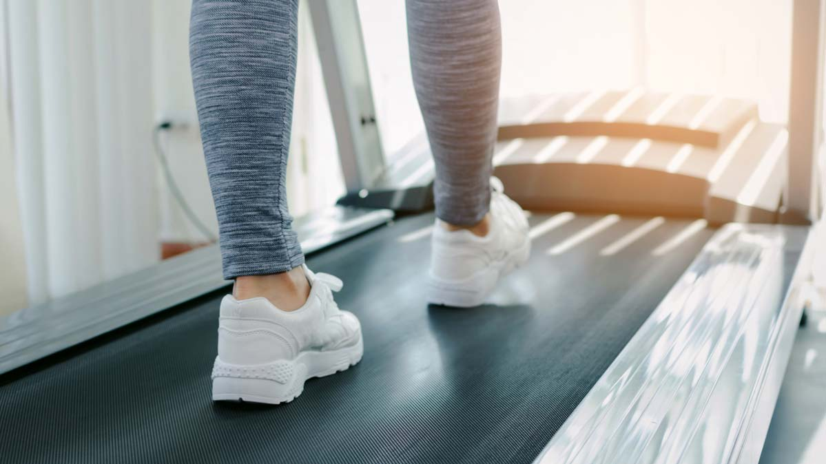 A woman in white sneakers and leggings walks on a treadmill