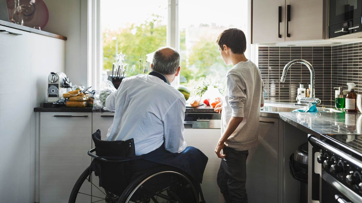 A man in a wheelchair and a boy in a kitchen
