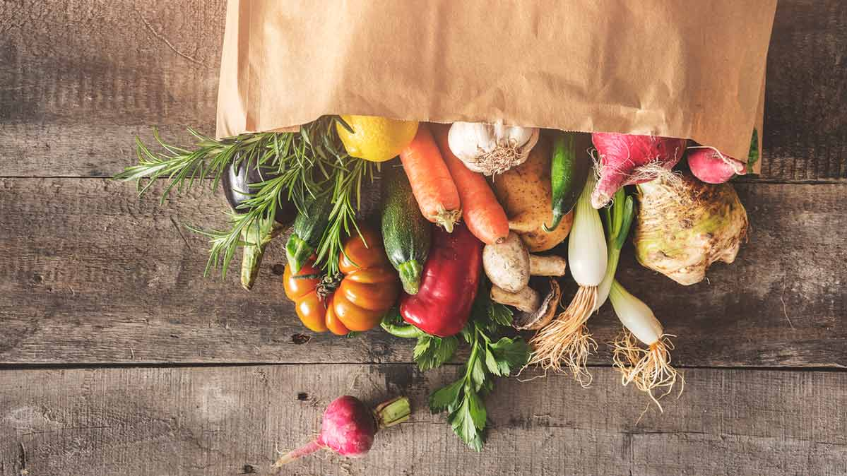 A grocery store bag filled with fresh produce