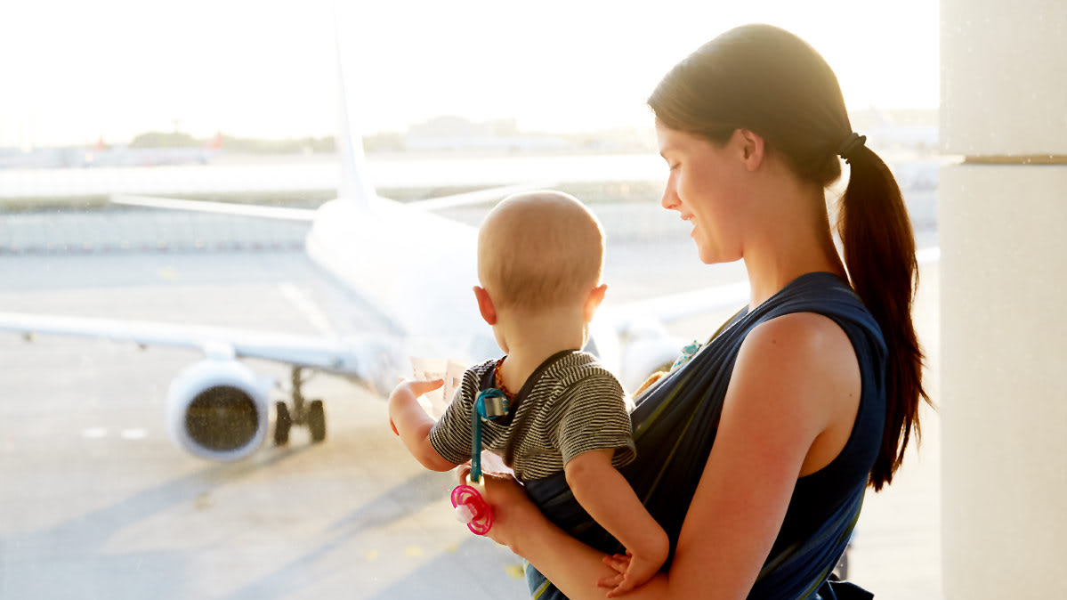 Woman with baby at an airport, waiting to fly