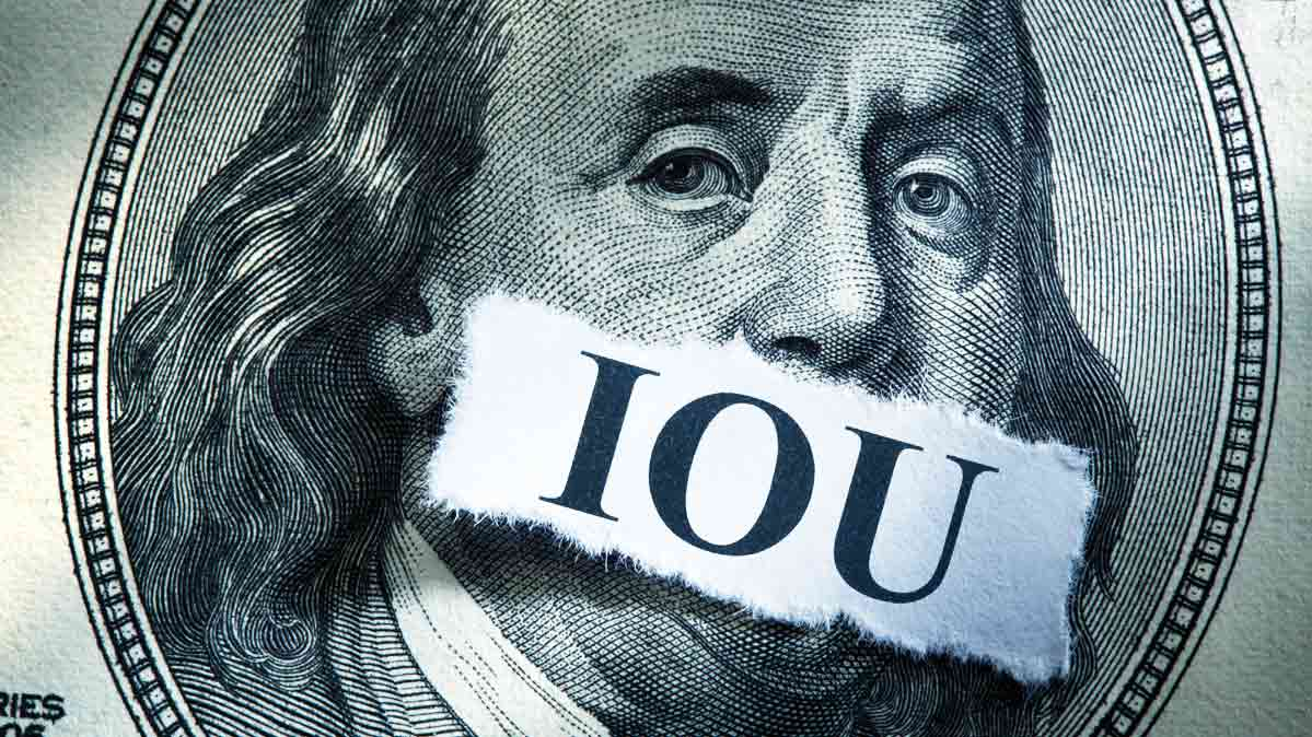 An illustration of a $100 bill showing Ben Franklin with an IOU sticker over his mouth