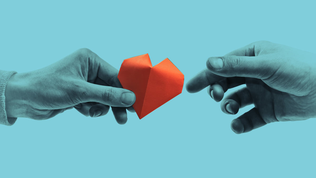 Photo showing one hand passing a charity symbolic paper heart to another hand