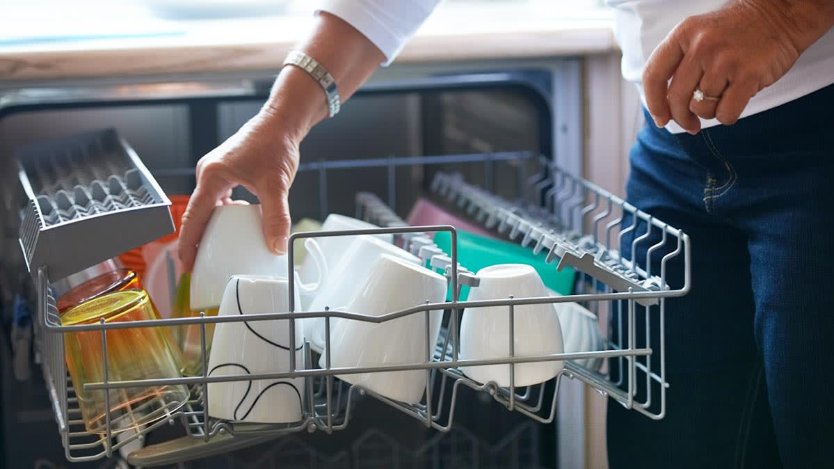 A person loading a dishwasher properly