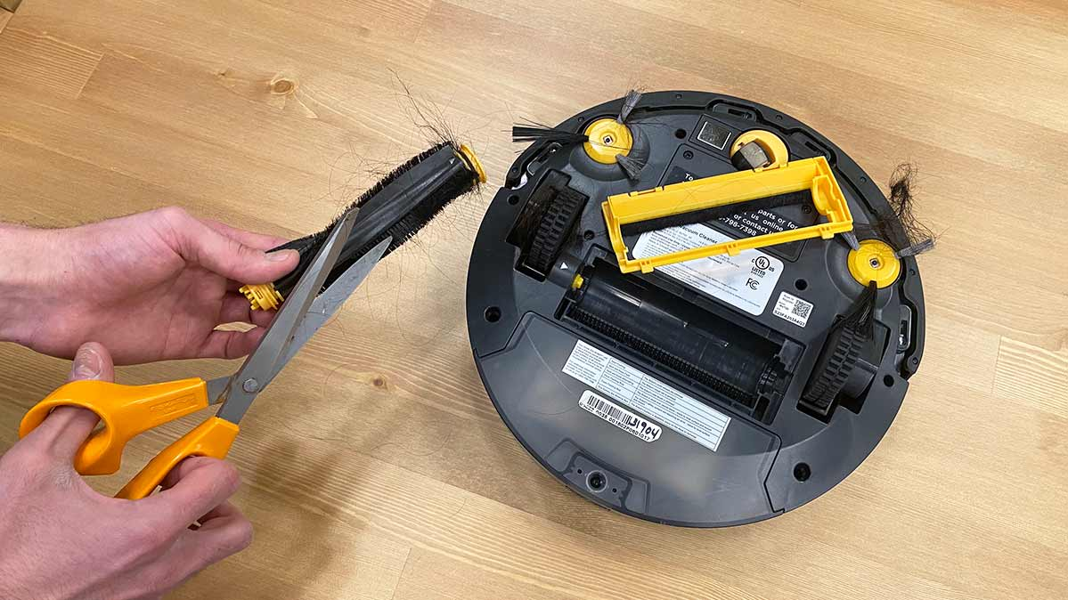 A tester removes hair with a pair of scissors to clean a robotic vacuum.