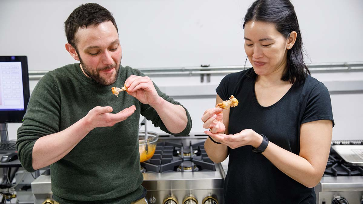 Two people standing side by side holding up partially eaten hot wings and smiling.