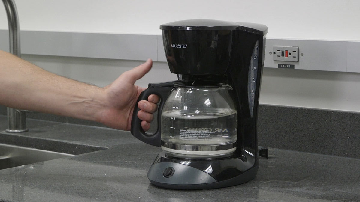 A coffee maker with a carafe full of water.