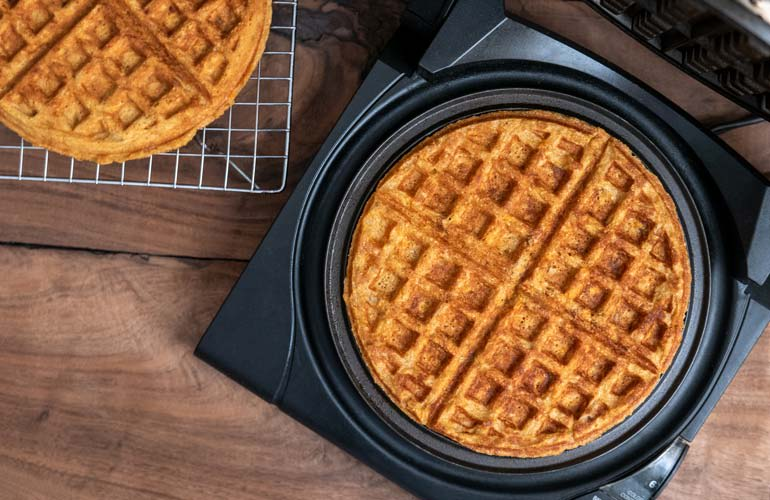 Waffles are cooking in the best waffle maker from Consumer Reports' tests.