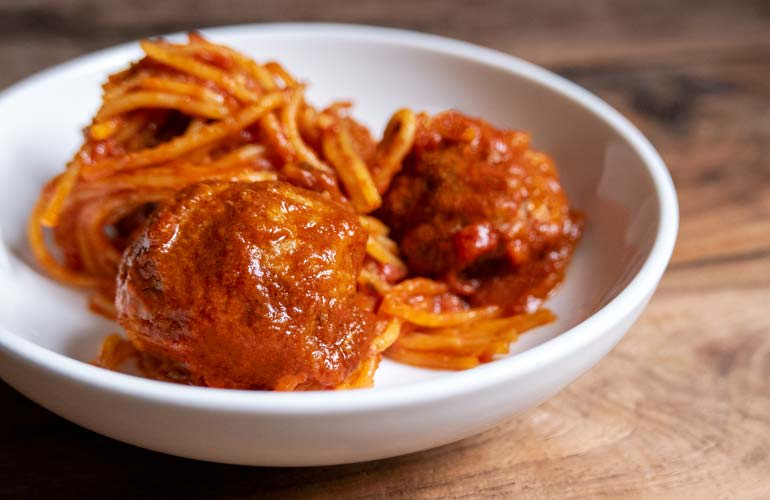 A bowl of spaghetti with meatballs, made in a multi-cooker from Consumer Reports' tests, is shown.