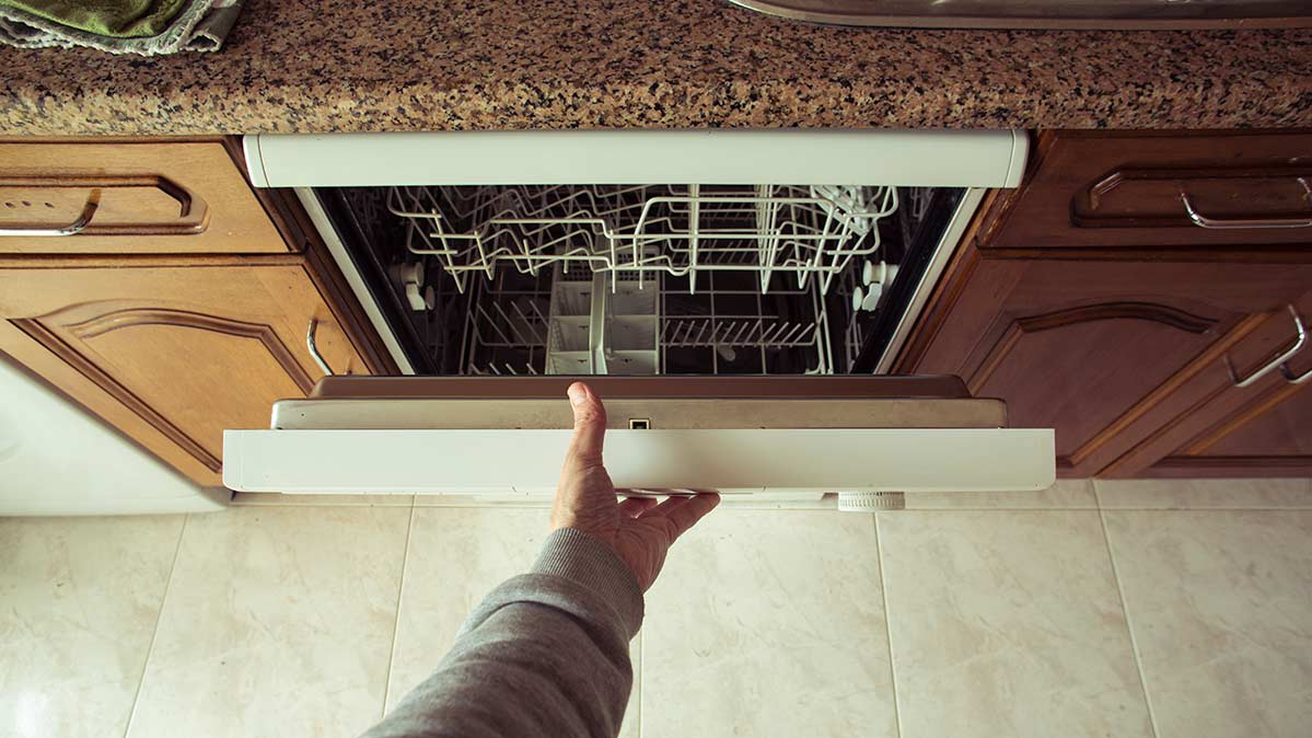 A hand on the slightly opened door of a dishwasher