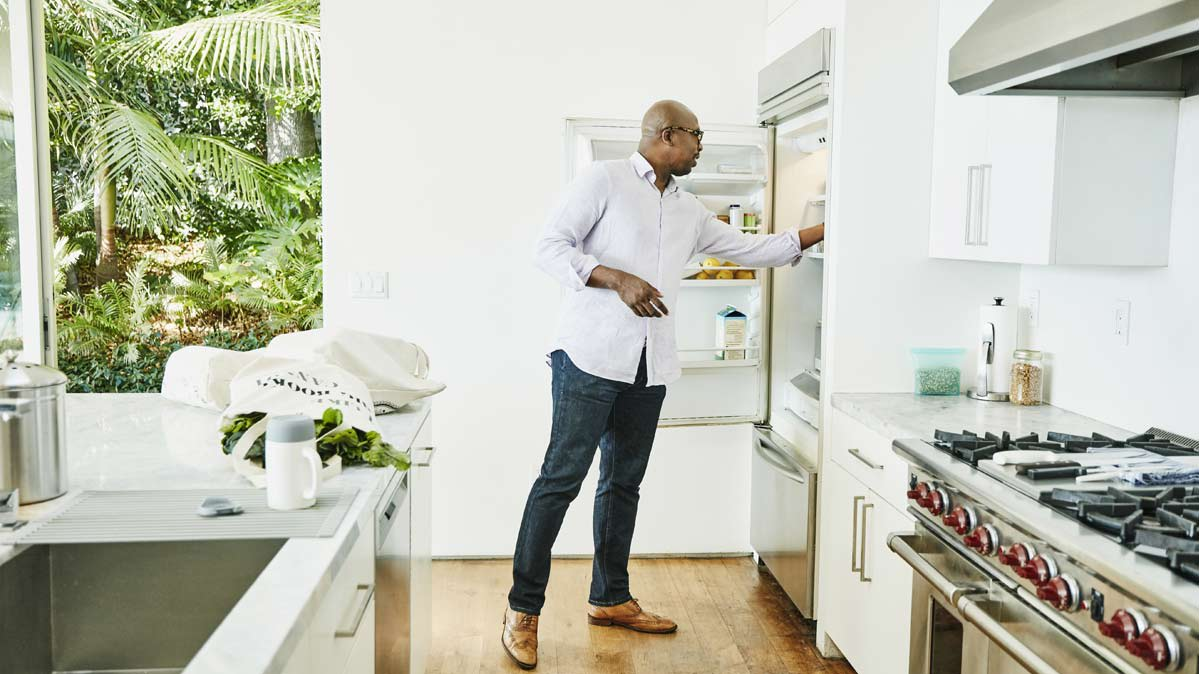 A man puts food in his refrigerator.