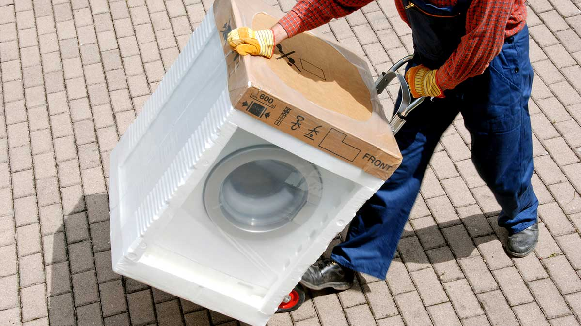 A brand-new washing machine appliance still in packaging being rolled on a dolly by a person.