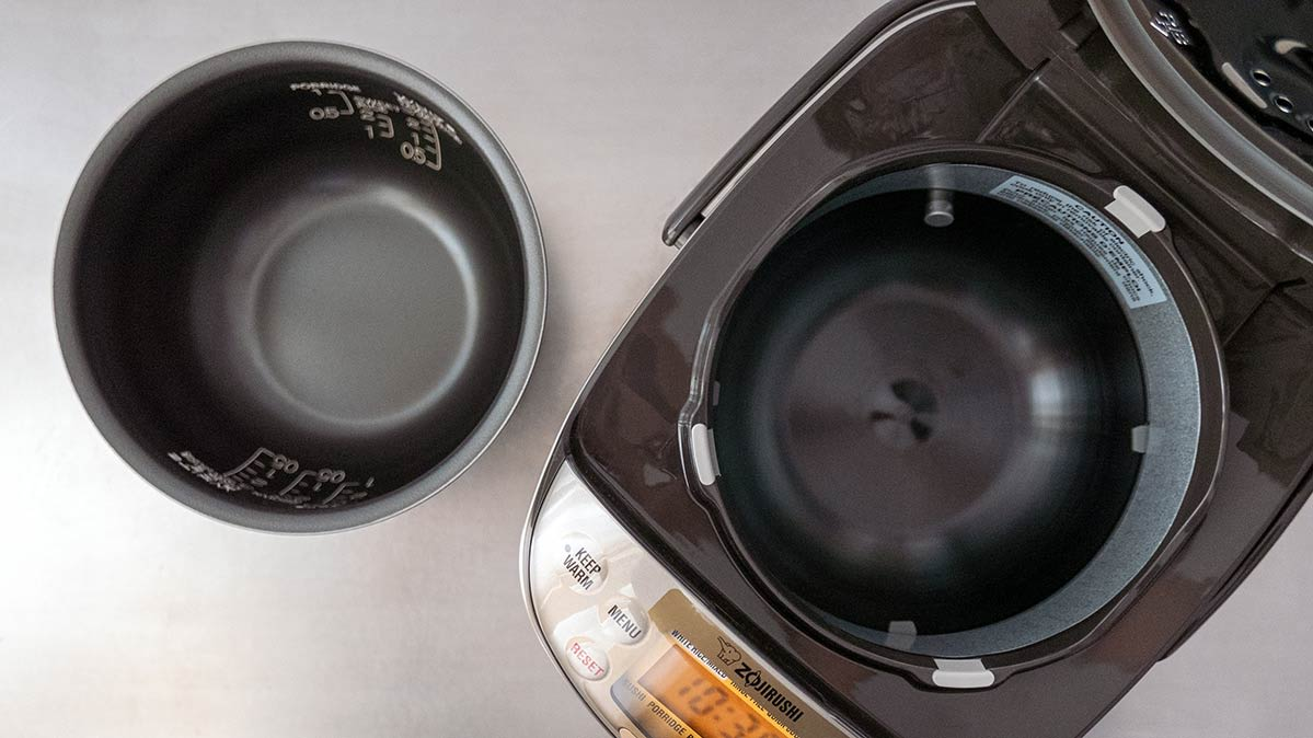 The inside of the Zojirushi rice cooker with the pot removed shows magnets along the sides, an essential part in induction heating.