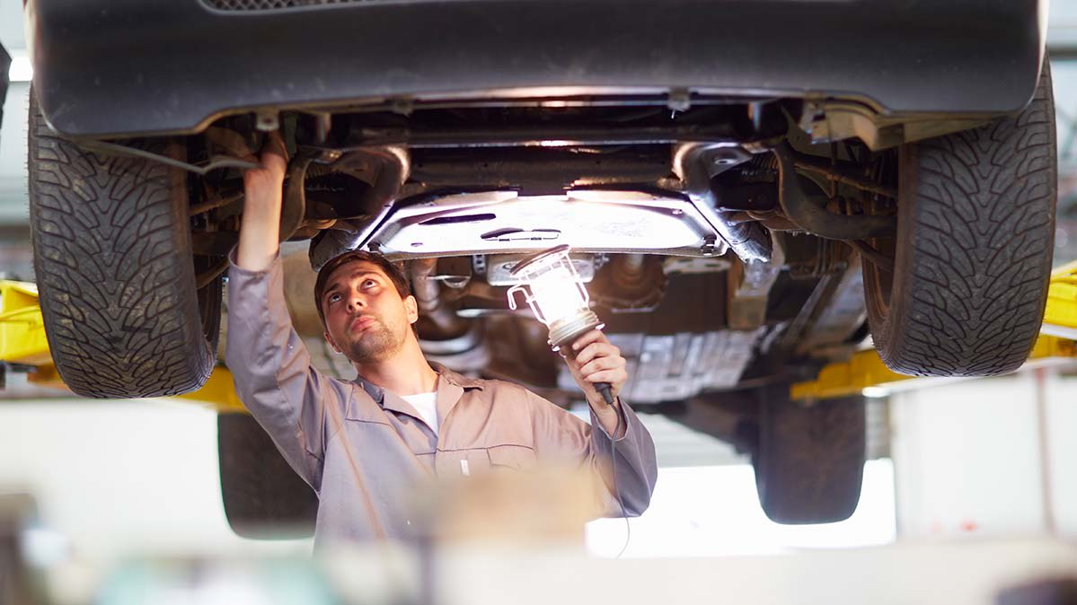 A mechanic checking the underside of a car that's on a lift