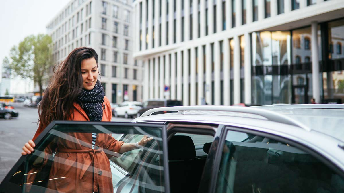 A woman entering a ride-share car picking her up
