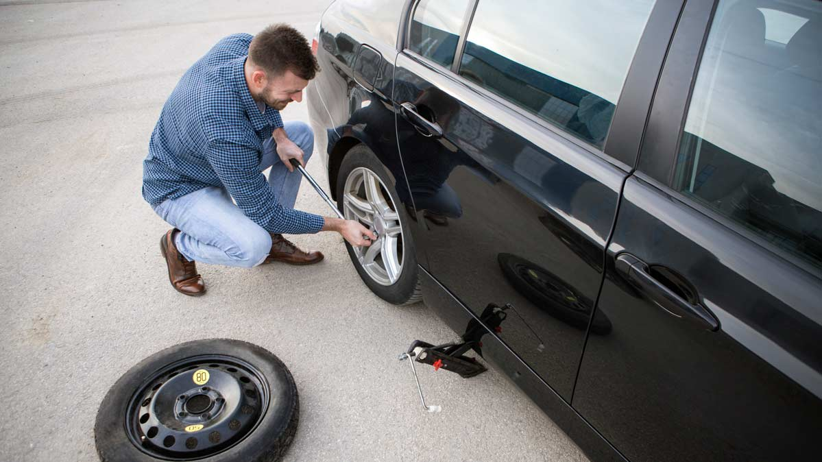 A person changing a flat tire