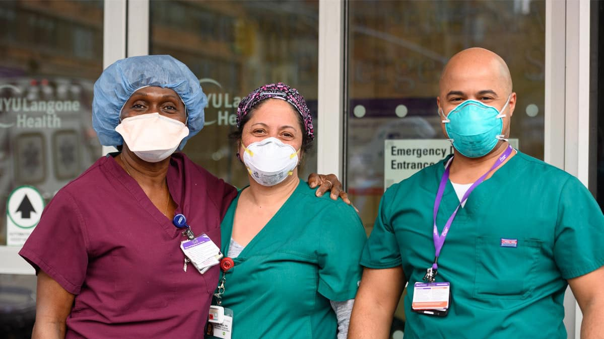 Three healthcare workers standing outside a medical facility