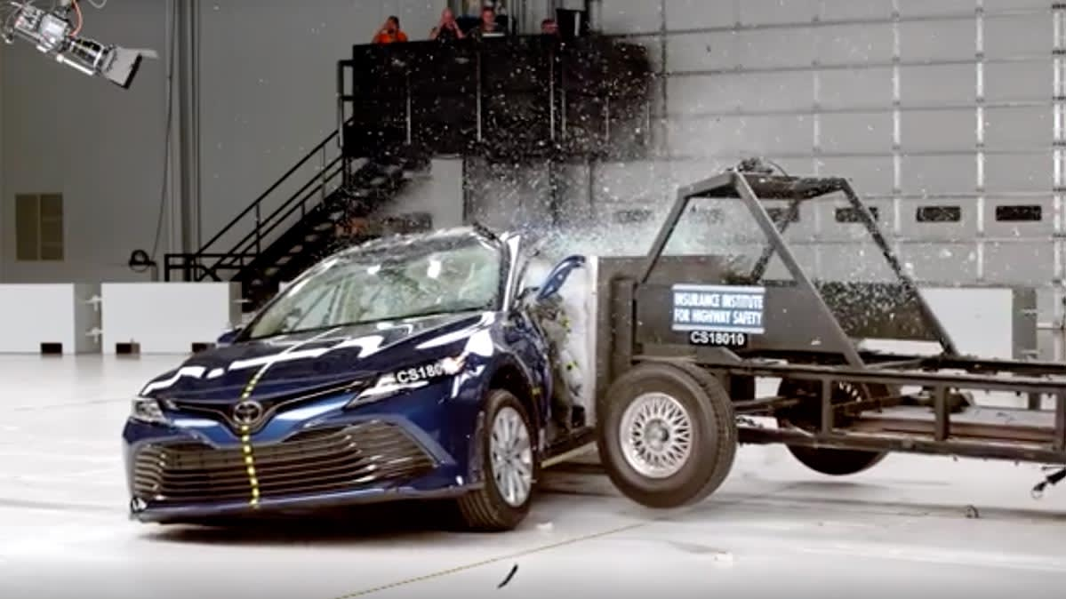 A Toyota Camry sedan being struck in the side by a large object as part of a crash test