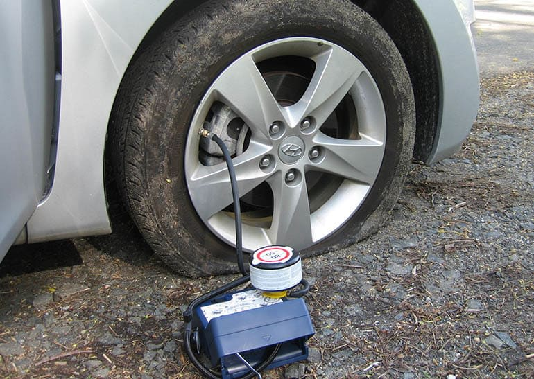 2011 Hyundai Elantra flat tire being repaired with a tire kit