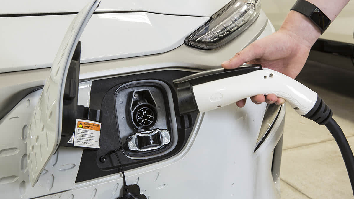 A person plugging a wall charger into an electric vehicle