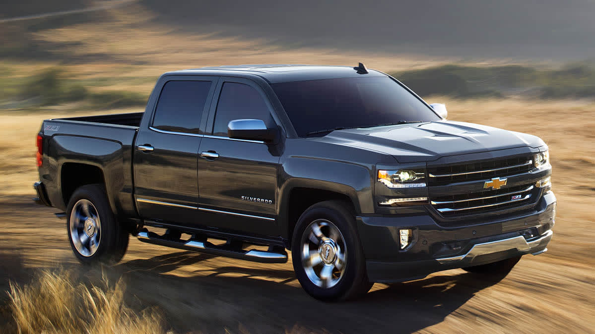 A 2018 Chevrolet Silverado pickup truck in black, driving across a desert. The Silverado is part of GM's latest recall for brake issues.