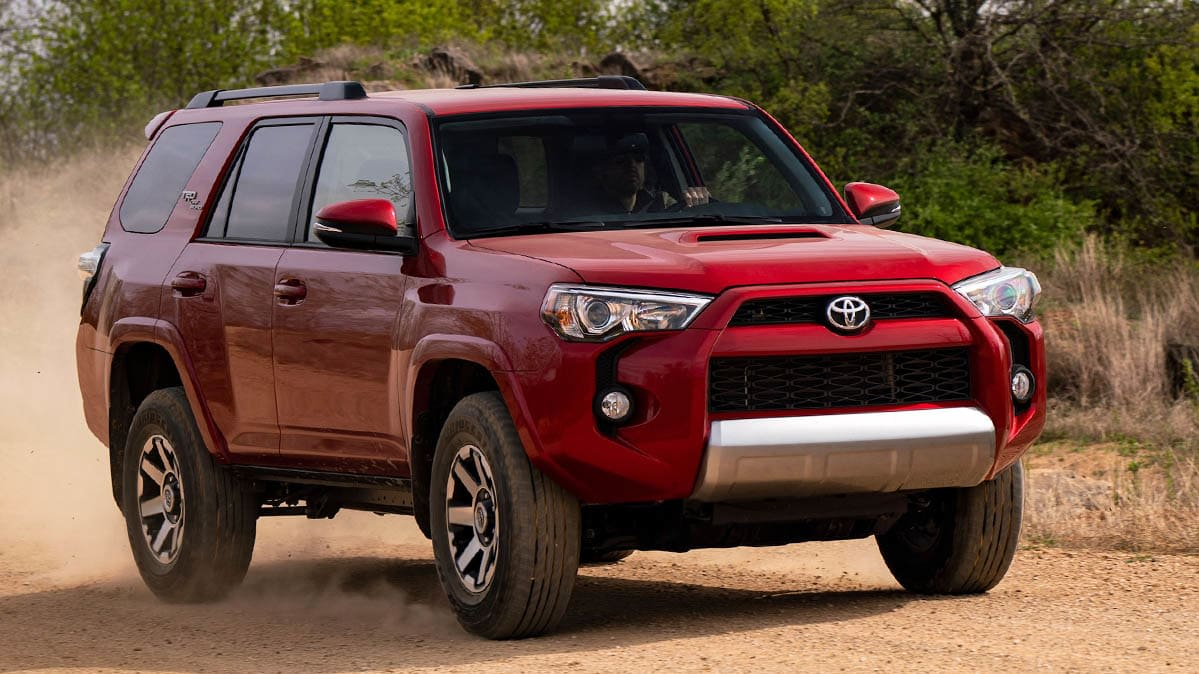 A 2018 red Toyota 4Runner SUV driving forward on the sand