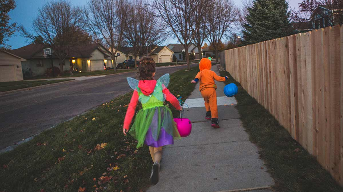 Two young trick-or-treaters in costume walking on a sidewalk alongside a wooden fence