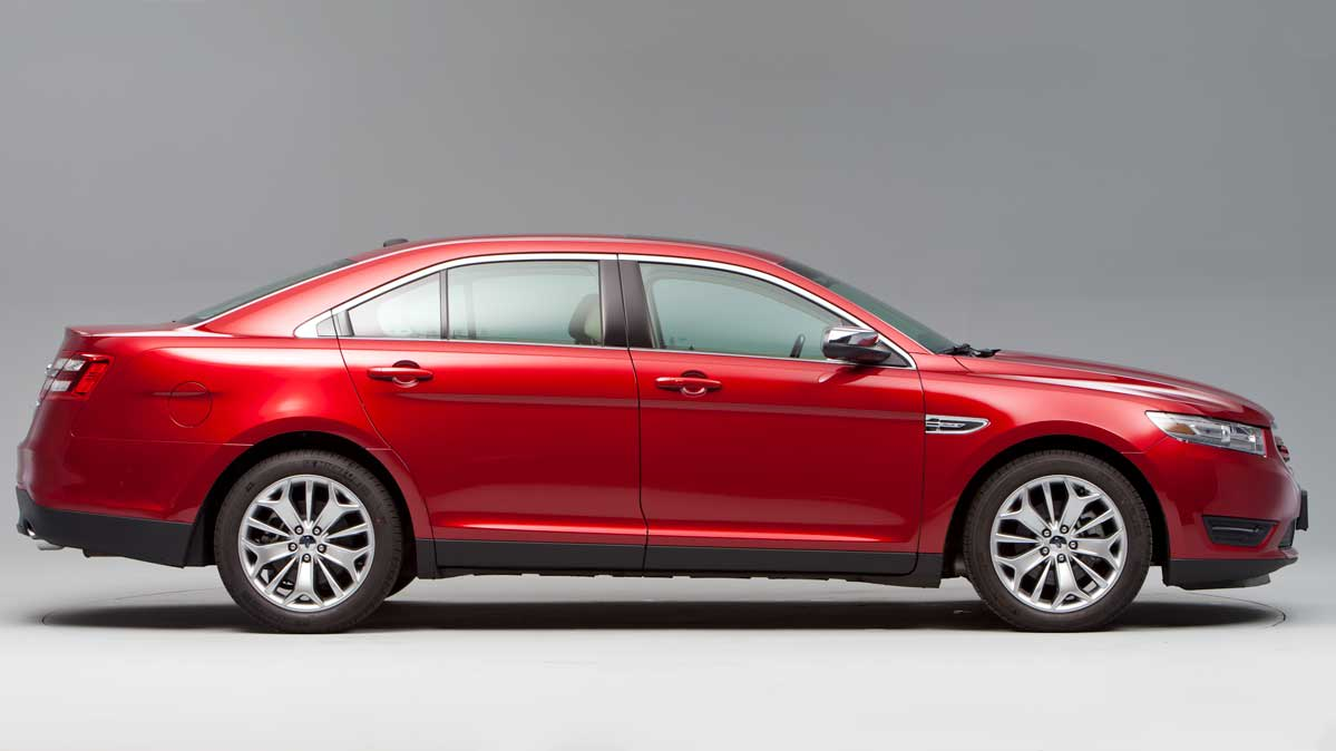 A 2014 Ford Taurus sedan in red, side view