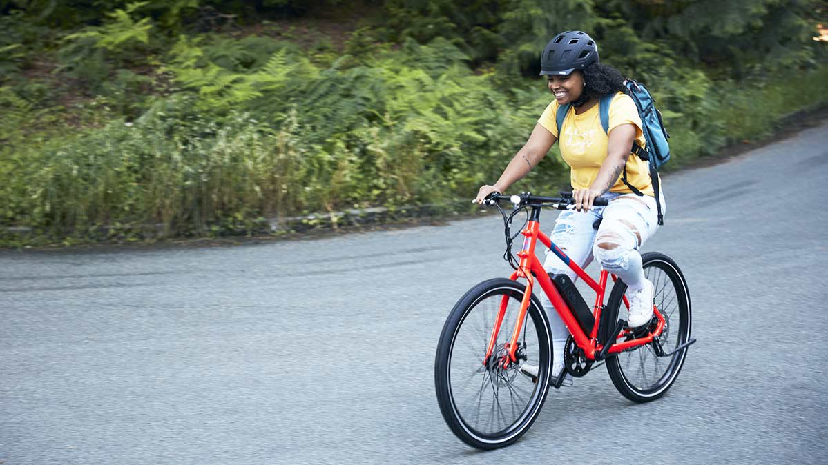 A person riding Rad Power Bike Mission 1 City Bike, a hybrid bicycle